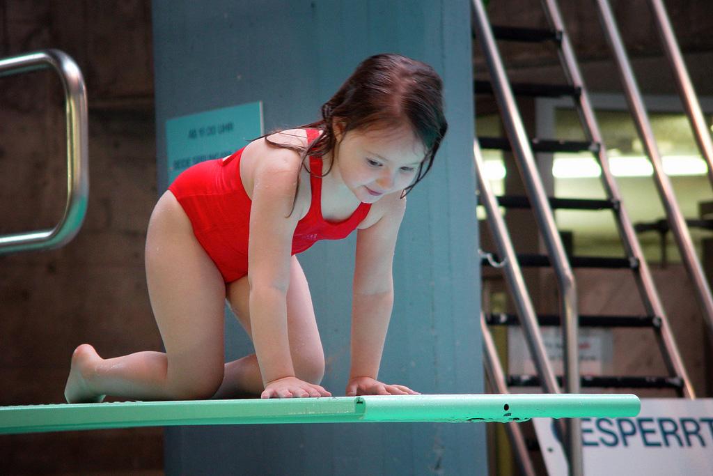 Kind springt im freibad vom 3 meter brett